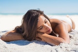 Beautiful woman lying on sand - 196996991