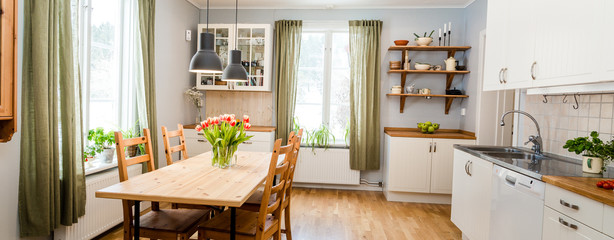banner of cozy kitchen interior with green curtains and red tulips on the wooden table © annaia