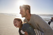Father With Daughter Having Fun On Winter Beach Together