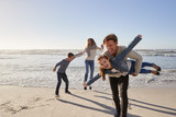 Parents With Children Having Fun On Winter Beach Together - 196998178