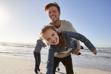 Father With Children Having Fun On Winter Beach Together