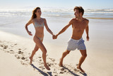 Couple On Summer Vacation Running Along Beach Together