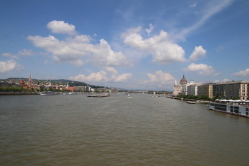 view on the danube river from a Budapest bridge, sunny day and clouds on blue sky