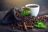 White black espresso Cup with pile of coffee beans and green leaves in bag on dark background