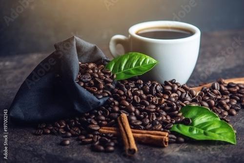 Biała czarna kawy espresso filiżanka z stosem kawowe fasole i zieleń liśćmi w torbie na ciemnym tle