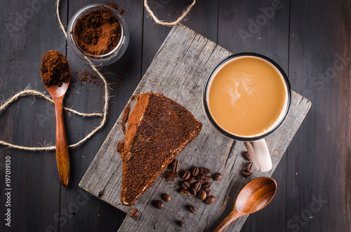 Poster cheese in ground coffee and a cup of cappuccino