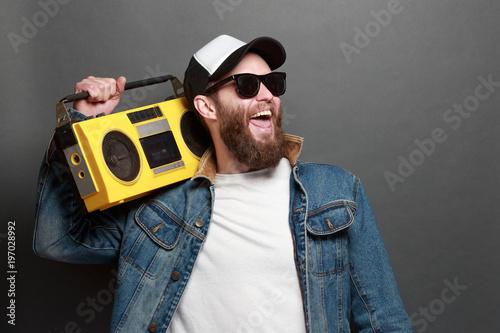 Fototapeta Hipster man listening to cassette player and singing along