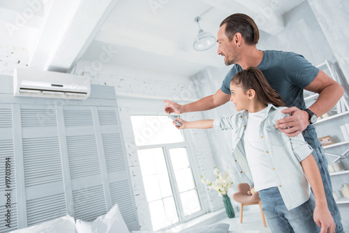 Comfortable temperature. Positive happy joyful man standing near his daughter and pointing at the air conditioner while teaching her how to use it