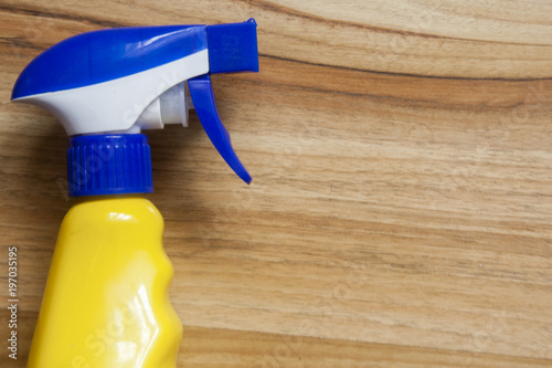 yellow-blue bottle of spraying glass on a wooden table background