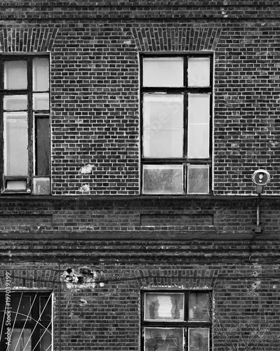 Fragment of the facade of an old brick building. High Windows and textured materials. Black and white styling. - 197039399