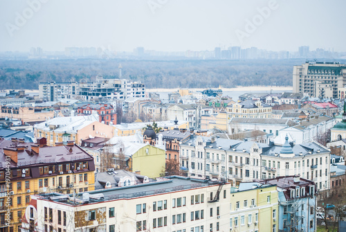 Foto op Plexiglas Kiev City of Kyiv (Kiev), capital of Ukraine, panorama. Colorful houses and Dnipro river on a background. Cloudy spring afternoon.