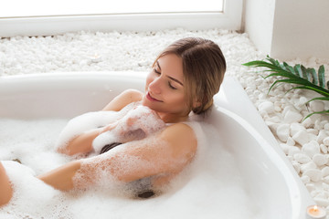Revitalize your beauty! Gorgeous good-looking young woman relaxing in bath with bath foam with serene smile and closed eyes. © stacestock