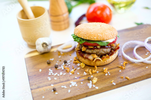 Homemade burger with beef, fried bacon and onion on wooden cutting board - 197054783