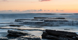 Rocky seashore seascape with wavy ocean during sunset - 197056550