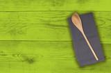 Kochlöffel und Küchentuch auf grünem Holz