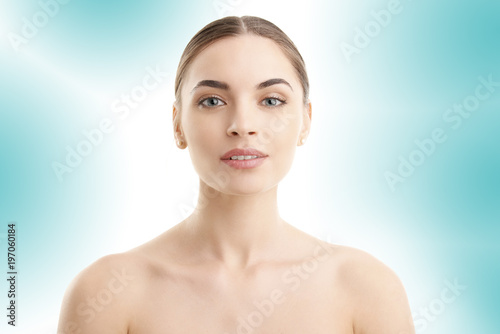 Flawless beauty. Close-up portrait of an attractive woman with perfect skin looking at camera while posing against at isolated light blue background.