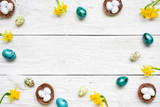 frame made of easter eggs, spring flowers and feathers on white wooden background. easter composition