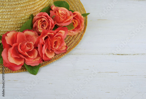 Closeup of a straw bonnet decorated with multiple silk roses on a white washed wooden background with copy space. Good for spring, summer, wedding or Kentucky Derby.