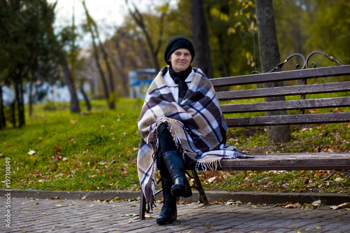 Poster Attractive middle aged woman covered with blanket sit on bench in spring day