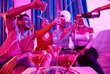 Low angle portrait of group of glamorous  people enjoying private party, sitting on sofa laughing happily while waitress pouring champagne to flute glasses - 197109515