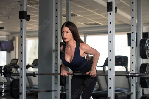 Woman Exercising Back With Barbell In The Gym