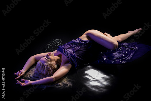 Sexy blonde lying in water in the dark
