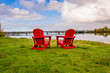 empty red chaise longues stand on the grass opposite the river