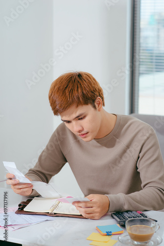 Unhappy asian man looking at bills sitting at table in living room - 197137996