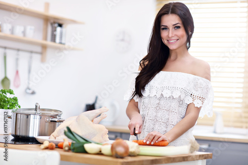 Young woman trying to prepare chicken soup in kitchen - 197167132