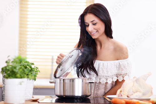 Young woman trying to prepare chicken soup in kitchen - 197167516