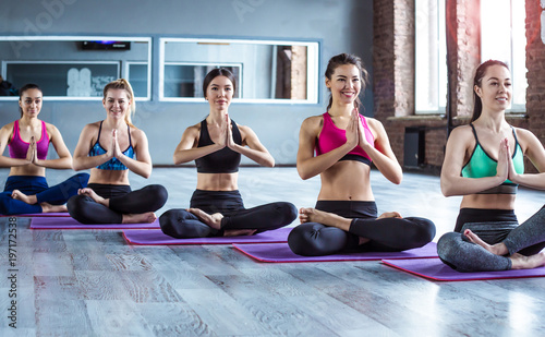 Fototapeta Multiracial Group of young women in sportswear doing yoga exercises with a coach or instructor. Class of yoga or fitness