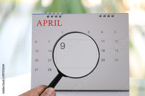 Poster Magnifying glass in hand on calendar you can look ninth day of month,Focus number nine in April