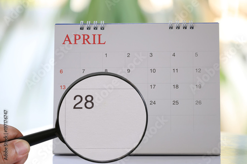 Poster Magnifying glass in hand on calendar you can look Twenty-eight day of month,Focus number Twenty-eight in April