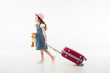 Little stylish tourist in hat with teddy bear and suitcase isolated on white, travel concept