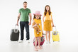 Upset little child with teddy bear and parents standing behind with suitcases isolated on white, travel concept