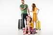 Upset little child sitting on suitcase while parents arguing isolated on white, travel concept