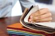 Tkaniny obiciowe. Kobieta ogląda kolory i wzory tkanin obiciowych.