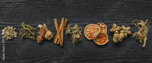 Dried herbs and Ginseng, Top view of Thai herbs and ginseng on wooden floor. Slices of dries root for make a herb juice on the dark table.