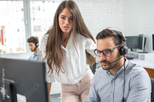 Customer support workers solving problems together on client's online account in call centre office.