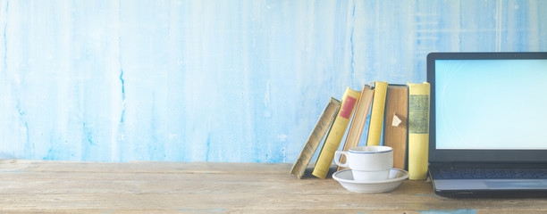 row of books,cup of coffee and laptop, learning, education, panorama, copy space © Thomas Bethge