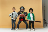 Three happy children show different sport. Studio fashion concept. Emotions concept.