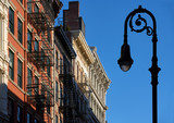 Soho building facades with cornices, fire escapes and a lamp-post. Manhattan, Soho, New York City - 197207516