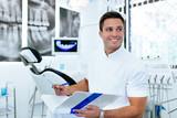 Handsome male dentist in doctors white lab coat posing in modern dental office