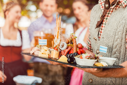 In Beer garden in Bavaria, Germany - beer and snacks are served, focus on meal