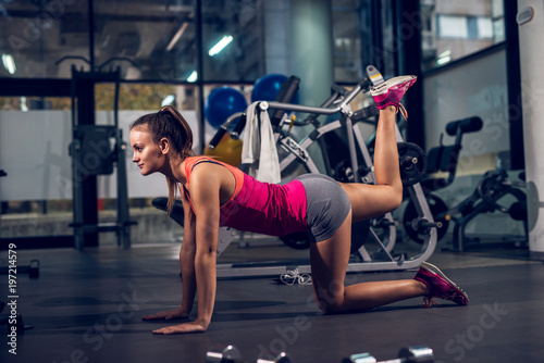 Fototapeta Side view of young focused satisfied attractive healthy sporty active shape girl doing legs exercises and warming while kneeling on the floor and raising one leg up in the gym.