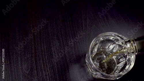 Whiskey pours into the glass on the table Slow Motion