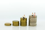 Miniature people:  Businessman sitting on the stack of coins read newspapers. Image use for business concept.