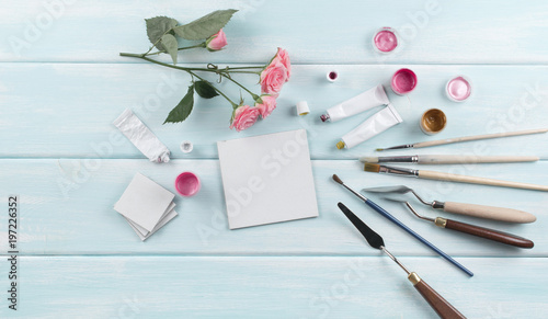Workplace with canvas, paintbrushes, roses and paints on wooden boards