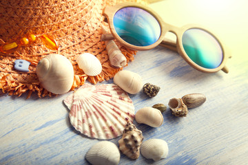 beach accessories glasses hat cockleshells on wood deck.