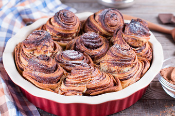 Yeast rolls with cinnamon decorated with sugar powder